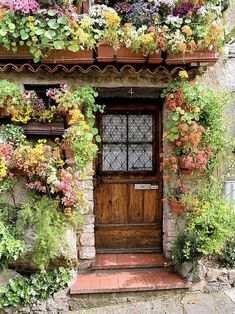 Beautiful flowers surrounding entry to house.