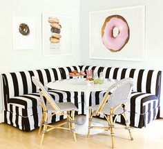 Playful contemporary kitchen showcase a stunning white and black stripped L-shaped banquette sat against walls holding white framed donut prints and behind a marble Saarinen dining table also seating two white and black french bistro dining chairs.