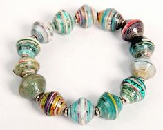 Colorful, recycled magazine paper beads are accented with silver rings in this fun stretchy bracelet. Wear one or stack several! The beads are coated with a cle