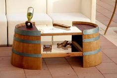 Coffee Table made from half a wine barrel. The top of the table utilizes the purple side of the barrel lid which was dyed naturally by the wine aged in the barrel. Two glass shelves borders by natural oak wood elongates the table, flatters it, and makes for an area to put magazines and decorative articles