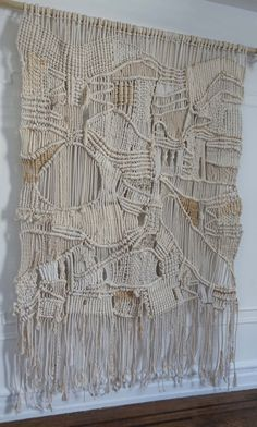 This wall hanging is made with intricate knots and weaves for a stunning effect. The ivory color palette and textural design are subtle yet rich with interest. Made from all natural silk, wool and cotton.  If you are interested in a variation of this design or a custom order please send me a message. Id be more than happy to discuss your requirements and create something special for you. M. xx  Size:  Height: 8 Width: 5 Cord width: 1/4- 3/4 ~ Beadwork available upon request. ~ Hanging pole…