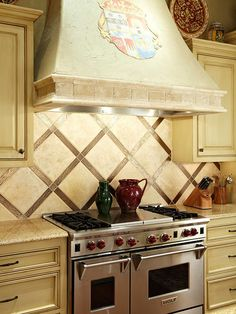 Nontraditional Arrangement-Cream backsplash tiles echo the color of the ceiling beams in this traditional kitchen. The bronze-hue accent tiles have metallic qualities that add a hint of shimmer. LOVE the family crest.