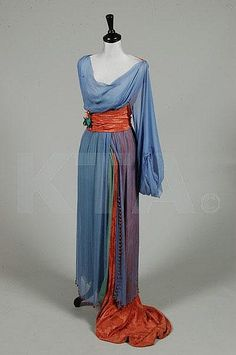 An unusual orientalist evening gown, circa 1913, the blue chiffon over-dress edged in large coral glass beads, single long sleeve, coral damask back bodice, waist sash with silk flowers and train, underskirt of jade green chiffon, together with a navy chiffon Paquin bodice, Winter 1912, London-Paris label no 51354, of midnight blue and ivory satin, chiffon and lace (2)