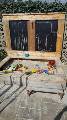 Krijtbordverf op de binnenkant van het houten deksel van de zandbak.