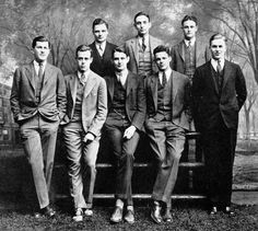 The Yale University Whiffenpoofs of 1927.  The cappella group embraces the fashions of the times with sharp, tailored three-piece suits. During the first half of the decade, trousers were very simple, straight and slightly narrow. The waistline dropped just below the belly button and would be worn with either a belt or suspenders. Creases down the front of the leg became popular for the first time, emphasising the silhouette. Cuffs were also added and could be seen a little bit shortened…