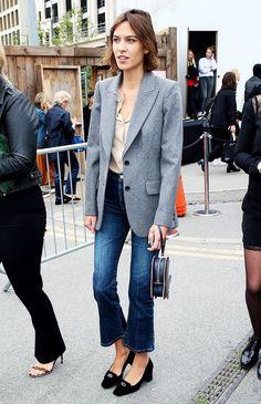 Alexa Chung wears a button-down shirt, blazer, jeans, and heels