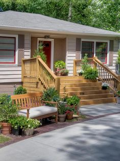 A wide wooden deck is perfect for entertaining while a matching wooden bench surrounded by container plants provides extra seating. Red window casings pop against brown raised panel shutters and match the red front door. Front Porch Deck, Porch Stairs, Front Stairs, Front Porch Design, Porch Railings, Small Front Porches, Front Courtyard, Porch Columns, Exterior Stairs