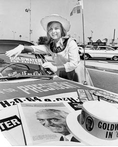 "A ""Barry Goldwater for President"" campaign volunteer posing for a portrait while decorating the campaign car in Van Nuys, September 23, 1964. Goldwater was an unsuccessful Republican nominee for President in 1964. San Fernando Valley Historical Society. San Fernando Valley History Digital Library."