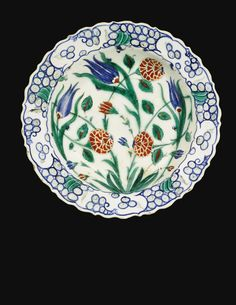 AN IZNIK POLYCHROME POTTERY DISH, TURKEY, 16TH CENTURY of shallow rounded form, decorated in underglaze cobalt blue, green and relief red with thin black outlines, featuring tulips and carnations emanating from a leafy tuft, the rim with a breaking wave motif, the reverse with flowerheads and leafy motifs