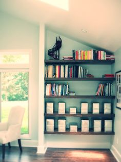 Bookshelves in a side alcove are a great way to utilize awkward wall space for additional storage. A design like this, with five simple, horizontal shelves, creates a perfect space to store and display collections in a creative and eye-catching way.