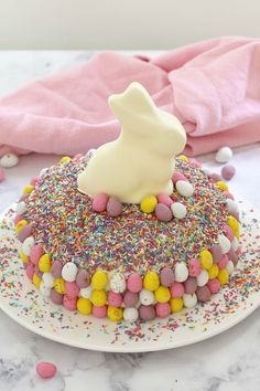 15 minutes is all it takes to whip up this show stopping EASY WHITE CHOCOLATE & MINI EGG EASTER CAKE. It looks AMAZING but is the simplest recipe ever!!! A store-bought white chocolatemud cake covered in white chocolate frosting, heaped with pretty sprinkles anddecorated with pastel chocolate Easter eggs and a white chocolate bunny… this really is the ultimate Easter cake!    #easter #cake #lindt #minieggs #recipe #easy #kids