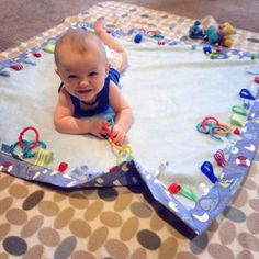Tummy time ribbon taggie and links play mat. available from facebook.com/wiggleguts #tummytime #playmat #baby