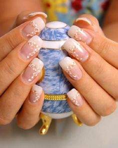 Glamorous looking white and gold nail art design. The white nail polish is used as the french tip color while embellishments are added on top that have gold accents with them.