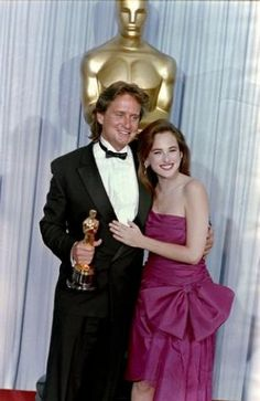 "1988: Actor Michael Douglas, accompanied by actress Marlee Matlin, poses with his Best Actor Oscar for the film ""Wall Street"""