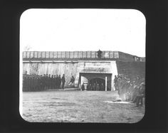 "Large group of soldiers stand on either side and at the entrance to Fort Wayne in Detroit, Michigan. Handwritten on mat front: ""Sally port of Fort and volunteers. 1861.""  (Burton Historical Col.)"