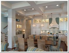 dark wood floors, white walls w/ board and batten, white kitchen, seagrass dining chairs, slipcovered furniture, rustic tables