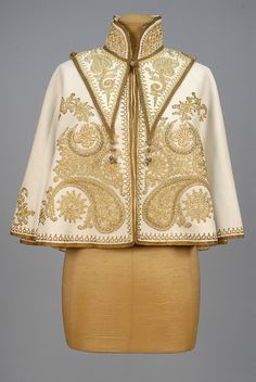 TWO-PIECE METALLIC EMBROIDERED CAPELET, EARLY 20th C. Cream felt with couched gold cord decoration of scrolls and botehs having satin stitch Persian script within two crescents set with turquoise stones, separate high cape collar having gold baubles with red bead at shoulder and tassels at front and back point, silk lining. L-20. $660