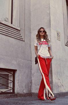 Look esportivo da Thassia Naves com camiseta trançada, calça esportiva vermelha e salto vermelho