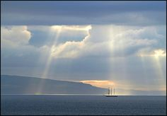 A tall ship caught in rays of sunlight in Portstewart Bay, County Londonderry, Northern Ireland.