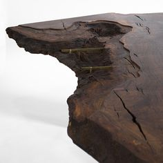 Live Edge Corset Dining Table / view of decayed Claro Walnut slab edge and brass Corsets which support the glass top.