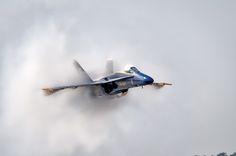 Angel De-cloaking - Blue Angel F/A-18 Hornet creates a vapor cone during a low level sneak pass. by Chris Buff 2012 air show