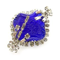 A beautiful brooch in the most unusual design. The brooch features a molded blue glass stone layered underneath metal prongs set with white...