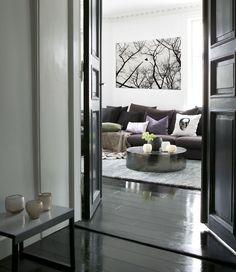 Черный ламинат и белые стены дополняет черно-белая картина