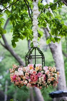 Hanging lantern wreathed in shades of pink roses and ivy vine