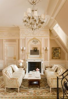 Breathtaking over the top French sophistication and feminine romantic decor in this suite at Ritz Paris with light pink, paneled walls, twin sofas, fireplace, and crystal chandelier. Marie Antoinette is written all over this girly hotel room!