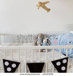 Mascots in white crib for newborn baby