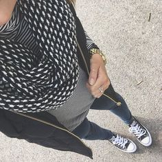 striped shirt, black puffer vest, black and white scarf, jeans, black converse