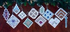 "NEWEST!    Sparkling Birthstone Ornaments showcases twelve different Hardanger designs.  Stitch them in the colors shown or choose one color scheme for a coordinated set.   The ornaments are a perfect size for stitching on the go!  The size of each ornament varies, but each one takes a 6"" x 6"" piece of 28-count fabric. Supplies required:  28-count White Cashel (3281-100)   Caron Collection Waterlilies: 233, 118, 249, 041"
