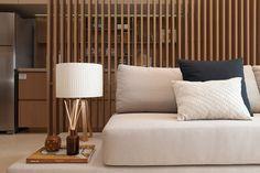 Decoração de apartamento pequeno e charmoso com ambientes integrados com ripas de madeira. Na sala sofá, adornos, plantas e luz natural.