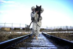 """""""Staff Sgt. Erick Martinez, a military dog handler uses an over-the-shoulder carry to hold his dog, Argo II, at Hill Air Force Base, Utah, on March 4. The exercise helps build trust, loyalty, and teamwork."""""""