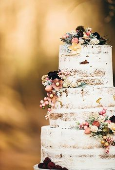 A semi-naked, three-tiered wedding cake with fresh berries and flowers in shades of peach, burgundy, green, and yellow, created by Sky's The Limit! Custom Cakes & More.