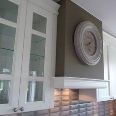 Kuchnia stylizowana, w której centralnym elementem jest zegar ozdabiający obudowę okapu.