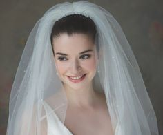 This subtle bouffant 2 tier Ivory Italian Tulle Wedding Veil from the Rainbow Club Collection encompasses modern & contemporary styling to accommodate all wedding budgets. It is perfectly created, comfortable & totally glamorous. It has a classic cut complimenting a sophisticated hand cut edge style. It features an array of crystals all over its tulle & a clear comb with soft pleating to complete the look. Why not add some rhinestones & crystals to create your own individual bespoke piece!