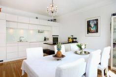 meubles de cuisine en blanc laqué, sol en parquet massif, lustre cristal et cadre décoratif