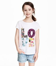 Short-sleeved top in cotton jersey with a print, slits in the sides and a slightly longer back section.