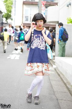 19-year-old Sayamo in Harajuku wearing a resale 101 Dalmatians t-shirt with a strawberry print skirt, Nincompoop Capacity knee socks, and New Balance sneakers from Pin Nap.