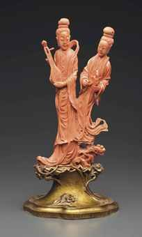 A CORAL CARVING OF TWO FEMALE MUSICIANS The coral branch is carved as two slender female musicians standing on a rockwork base from which sprouts lingzhi and peony, each wearing long, layered robes and scarves, and with hair in a topknot, one holding a pipa, the other a sheng mouth organ. 11 in. (28 cm.) high