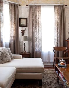Natural burlap curtains clear glazed plaster walls create a modern yet softly weathered look.