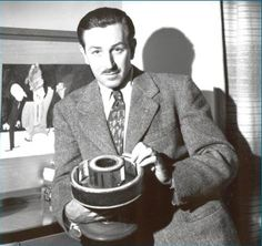Walt Disney with an early motion picture machine called a Praxinoscope.