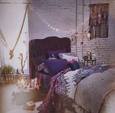 love this room- exposed brick painted white, lush fabrics, tons of pillows and light streaming in, candles- bohemian magic