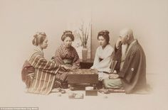 Pictured: A group, apparently a family, playing the popular game Go in Yokohama. Go, an ancient board game invented in China about 2,500 years ago, involves moving small stones around a flat surface in an attempt to encircle an opponent. It was considered an essential art for the upper classes