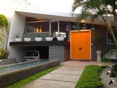 Mid Century Modern exterior with orange front door, white cement planters, multilevel.