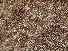 L'artiste installé à Londres Rowan Mersh utilise des milliers de petits coquillages qu'il assemble délicatement un par un pour créer des surfaces qui ont l'air naturelles de textures ondulantes.