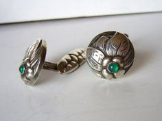 Here is a rare pair of Georg Jensen cufflinks. The design is early Danish Art Nouveau by Georg Jensen himself, probably from the first decade of the 20th century. They feature a small flower with a tiny chrysoprase at its heart.
