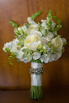 White and green bouquet of hydrangea, garden roses, cymbidium orchids, snapdragons, freesia, and hypericum berries with gold accent on the wrap | floral design by Andrea Layne Floral Design | photography by Aaron Bornfleth | event planning by Confetti Events