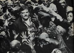 "George Romero surrounded by his undead during the filming of ""Day of the Dead."""